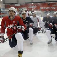 Photo - Washington Capitals Alex Ovechkin of Russia, second from left, and his teammates listen to coach Adam Oates during NHL hockey team practice at the Kettler Capitals Iceplex in Arlington, Va. Wednesday, May 1, 2013. The Capitals host the New York Rangers in Game 1 of a first-round NHL hockey Stanley Cup playoff series on Thursday. (AP Photo/Susan Walsh)