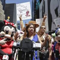 Photo - Lucia Gomez, center, executive director of La Fuente, speaks during a press conference, Tuesday, Aug. 19, 2014 at Times Square in New York. Gomez lead the gathering that called for the fair treatment and the right for performers to work as costumed characters. Gomez said,