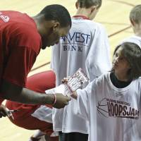 Photo - Taryn Phillips, right, age seven, of Blanchard, Okla., asks Oklahoma's Romero Osby, left, for an autograph, following an open