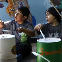 Photo - CHILD / KIDS: Francisco Ruiz, left, and Joseph Mijares beat on empty buckets with drumsticks during a music session led by Armando Rivera.  Church volunteers work with children at this week's  fall break art and music camp at Hillcrest Fuente de Vita on Tuesday, Oct. 16, 2012.  The camp, called