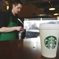 Photo - FILE - In this Friday, April 27, 2012, photo, a Starbucks drink waits for a customer to pick it up as barista Josh Barrow prepares another, in Seattle. Starbucks CEO Howard Schultz wants lawmakers to come together to resolve their political gridlock. From Wednesday, Oct. 9, 2013, to Friday, Oct. 11, 2013, the coffee chain is offering a free tall brewed coffee to any customer in the U.S. who buys another person a beverage at Starbucks. (AP Photo/Ted S. Warren, File) ORG XMIT: NY207