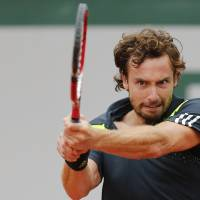 Photo - Latvia's Ernests Gulbis returns the ball during the third round match of the French Open tennis tournament against Radek Stepanek of the Czech Republic at the Roland Garros stadium, in Paris, France, Friday, May 30, 2014.  (AP Photo/David Vincent)