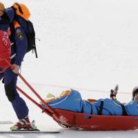 Photo - Andorra's Joan Verdu Sanchez is carried away by medics after he crashed in the first run of the men's giant slalom at the Sochi 2014 Winter Olympics, Wednesday, Feb. 19, 2014, in Krasnaya Polyana, Russia. (AP Photo/Gero Breloer)