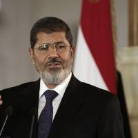 Photo -   FILE - In this Friday, July 13, 2012 file photo, Egyptian President Mohammed Morsi speaks to reporters during a joint news conference with Tunisian President Moncef Marzouki, unseen, at the Presidential palace in Cairo, Egypt. Egypt's Islamist president has appointed on Tuesday, Sept. 4, 2012, 10 new governors, four of them leading members of his fundamentalist Muslim Brotherhood group. The Islamist-led upper house of parliament, the Shura Council, also appointed ultraconservative Islamists as members of state-run human rights and media councils. Egypt is divided into 27 provinces or governorates, each headed by a governor. Of the 10 governors appointed by President Mohammed Morsi on Tuesday, four are Muslim Brotherhood members and three are former army generals.(AP Photo/Maya Alleruzzo, File)