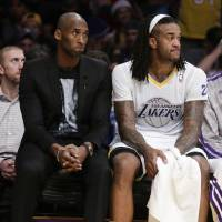 Photo - Los Angeles Lakers guard Kobe Bryant, left, and Jordan Hill sift on the bench during the first half of the Lakers' NBA basketball game against the Miami Heat in Los Angeles, Wednesday, Dec. 25, 2013. (AP Photo/Chris Carlson)