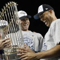 Photo - FILE - In this Nov. 4, 2009, file photo, New York Yankees' Derek Jeter, left, and Mariano Rivera look at the championship trophy after winning the Major League Baseball World Series against the Philadelphia Phillies, in New York. Jeter says he will retire after this season