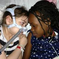 Photo - FILE - In this May 30, 2013 file photo provided by the Murnaghan family, Sarah Murnaghan, left, lies in her hospital bed next to adopted sister Ella on the 100th day of her stay in Children's Hospital of Philadelphia. Murnaghen, whose efforts to qualify for an organ donation drew public debate over how donated lungs are allocated was getting a transplant Wednesday, June 12, 2013, at Children's Hospital of Philadelphia, her family said. (AP Photo/Murnaghan Family, File)