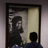 Photo - A woman visiting the John F. Kennedy Presidential Library and Museum views a display of the flag that draped Kennedy's casket and a photo of Jacqueline Kennedy during the funeral Friday Nov. 22, 2013 in Boston. Kennedy, the 35th President of the United States, was assassinated in Dallas 50 years ago today. (AP Photo/Stephan Savoia)