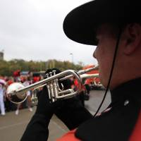 Photo - An OSU band member plays during the walk during the college football game between Oklahoma State University (OSU) and the University of Kansas (KU) at Memorial Stadium in Lawrence, Kan., Friday, Oct. 12, 2012. Photo by Sarah Phipps, The Oklahoman