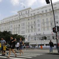 Photo - Pedestrians cross a street in front of the Copacabana Palace where Ray Whelan, of MATCH Services, is staying, in Rio de Janeiro, Brazil, Tuesday, July 8, 2014. The World Cup corporate hospitality executive was arrested at the Copacabana Palace Monday, the hotel used by FIFA officials during the World Cup. Whelan, who is suspected of involvement with a ticket-scalping ring, was released from prison early Tuesday. (AP Photo/Leo Correa)