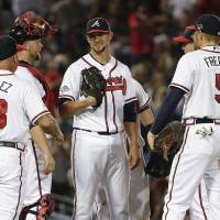 Photo - Atlanta Braves starting pitcher Mike Minor, center, speaks to catcher Brian McCann, second from left, and other teammates in the seventh inning during Game 2 of the National League division series against the Los Angeles Dodgers, Friday, Oct. 4, 2013, in Atlanta. (AP Photo/John Bazemore)
