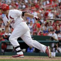 Photo - St. Louis Cardinals' Matt Holliday follows through on a two-run single during the eighth inning of a baseball game against the Chicago Cubs, Sunday, Aug. 31, 2014, in St. Louis. The Cardinals won 9-6. (AP Photo/Jeff Roberson)