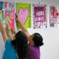 Photo - Brenda Castaneda, left, and Irma Castaneda, right, help the nonprofit art organization 29 Pieces hang art in the hallways at Parkland Memorial Hospital, Saturday Sept. 21, 2013 in Dallas. About 30,000 works of art reflecting on love will be displayed throughout Dallas this fall to commemorate the 50th anniversary of the assassination of President John F. Kennedy. (AP Photo/29 Pieces)