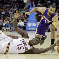 Photo - Cleveland Cavaliers' Anthony Bennett (15) bats a loose ball away from Los Angeles Lakers' Kendall Marshall in the fourth quarter of an NBA basketball game on Wednesday, Feb. 5, 2014, in Cleveland. The Lakers won 119-108. (AP Photo/Mark Duncan)