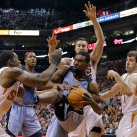 Photo - Memphis Grizzlies' Tony Allen, center, is pressured by Phoenix Suns' Eric Bledsoe, left, Miles Plumlee, rear, and Goran Dragic, of Slovenia, during the first half of an NBA basketball game, Monday, April 14, 2014, in Phoenix. (AP Photo/Matt York)
