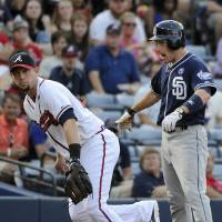Photo - San Diego Padres' Chris Denorfia, right, stands at third base near Atlanta Braves' Chris Johnson after advancing on a single by Yangervis Solarte during the first inning of a baseball game Friday, July 25, 2014, in Atlanta. (AP Photo/David Tulis)