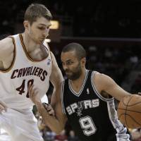 Photo - San Antonio Spurs' Tony Parker (9) drives past Cleveland Cavaliers' Tyler Zeller (40) during the first quarter of an NBA basketball game Wednesday, Feb. 13, 2013, in Cleveland. (AP Photo/Tony Dejak)