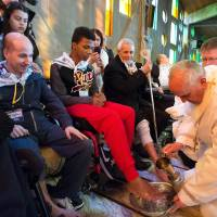 "Photo -  In this picture made available by the Vatican newspaper L'Osservatore Romano, Pope Francis washes the foot of a man at the Don Gnocchi Foundation Center Thursday in Rome. The pontiff washed the feet of 12 elderly and disabled people — women and non-Catholics among them — in a pre-Easter ritual designed to show his willingness to serve like a ""slave."" AP Photo/L'Osservatore Romano"