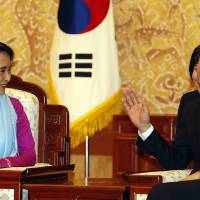 Photo - Myanmar opposition leader Aung San Suu Kyi, left, talks with South Korean President Lee Myung-bak at the presidential Blue House in Seoul, South Korea Tuesday, Jan. 29, 2013. During her five-day trip, Suu Kyi is scheduled to attend the opening of the Special Olympics, a biennial global event that South Korea is hosting in the alpine town of Pyeongchang for the first time, organizers of her trip say. The 1991 Nobel Peace Prize laureate will then receive a human rights award in the city of Gwangju, where a 1980 uprising was crushed with deadly force by the then-military government. (AP Photo/Lee Jae-won, Pool)