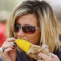 Photo - Crystal Wilkerson of Deer Creek bites into an ear of roasted corn  at the Oklahoma State Fair on Wednesday,  Sep. 18, 2013. Wilkerson attended the fair with about a dozen residents from the Grace Living Center in Bethany, where Wilkerson works as a social worker. Photo  by Jim Beckel, The Oklahoman.