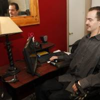 Photo - Brandon Coats works on his computer at his home in Denver on Thursday, Dec. 6, 2012. The Colorado case of Brandon Coats is giving employers pause. Coats, 33, was a telephone operator for Dish Network. Paralyzed as a teenager in a car crash, he's also been a medical marijuana patient in Colorado since 2009. He was fired in 2010 for failing a company drug test, though the employer didn't claim he was ever impaired on the job. Coats sued, and the case is pending before the Colorado Court of Appeals. The case will test the bounds of Colorado's Lawful Off-Duty Activities Law, which says workers can't be dismissed for legal behavior off the clock. It was enacted in 2007 to protect tobacco users. (AP Photo/Ed Andrieski)