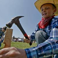 Photo - Weston Rutledge drives the stake into the ground to claim land during the Oklahoma Land Run celebration at Mustang Trails Elementary on Monday, April 22, 2013, in Mustang, Okla.   Photo by Chris Landsberger, The Oklahoman