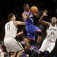 Photo - Philadelphia 76ers' Jrue Holiday, center, looks to pass past Brooklyn Nets' Brook Lopez, left, and Gerald Wallace during the first half of an NBA basketball game at the Barclays Center Sunday, Dec. 23, 2012 in New York.  (AP Photo/Seth Wenig)