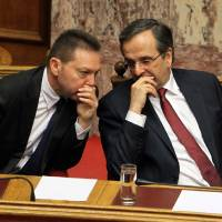 Photo -   Greece's Prime Minister Antonis Samaras, right, speaks to Finance Minister Yannis Stournaras during a parliament meeting for vote on 2013 country's budget in Athens, Sunday, Nov. 11, 2012. Greece's lawmakers were set today to pass next year's austerity budget, extending tough spending cuts measures that have already left Greeks struggling as the country tries to slash its debts and pull itself out of a severe recession.(AP Photo/Thanassis Stavrakis)