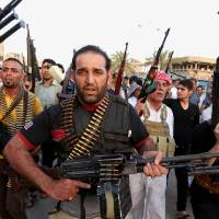 Photo - Iraqi Shiite tribal fighters deploy with their weapons while chanting slogans against the al-Qaida-inspired Islamic State of Iraq and the Levant (ISIL),  to help the military, which defends the capital in Baghdad's Sadr City, Iraq, Friday, June 13, 2014. The tribal leaders met in Sadr city on Friday and declared their readiness along with their tribesmen to take up arms against the al-Qaida inspired group that had in Iraq's made advance Sunni heartland.(AP Photo/ Karim Kadim)
