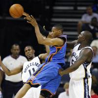 Photo - Oklahoma City Thunder guard Russell Westbrook, center, gets a pass off under pressure from Memphis Grizzlies defenders Michael Conley, left, and Zach Randolph during the second half of a preseason NBA basketball game Wednesday, Oct. 7, 2009, in Memphis, Tenn. The Grizzlies won 99-91. (AP Photo/Lance Murphey) ORG XMIT: TNLM110