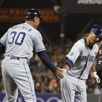 Photo - San Diego Padres' Tommy Medica, right, is greeted by third base coach Glenn Hoffman after hitting a home run off San Francisco Giants relief pitcher Javier Lopez in the eighth inning of a baseball game Tuesday, June 24, 2014, in San Francisco. (AP Photo/Eric Risberg)