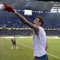 Photo - Bayern's Mario Mandzukic of Croatia points to his fans after scoring three goals in the  quarterfinal match of the German soccer cup between Hamburger SV and Bayern Munich in Hamburg, Germany, Wednesday, Feb. 12, 2014. (AP Photo/Martin Meissner)