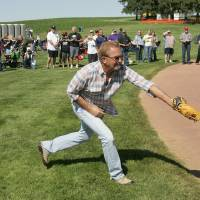 Photo - Actor Kevin Costner makes a back-handed catch as he plays catch with his sons during a party celebrating the 25th anniversary of the