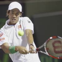 Photo - Kei Nishikori of Japan, returns a shot from Roger Federer of Switzerland, at the Sony Open Tennis tournament, Wednesday, March 26, 2014 in Key Biscayne, Fla. (AP Photo/Wilfredo Lee)
