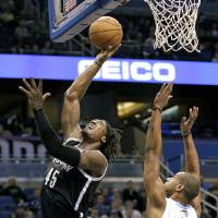 Photo - Brooklyn Nets' Gerald Wallace (45) takes a shot in front of Orlando Magic's Arron Afflalo (4) during the first half of an NBA basketball game, Friday Nov. 30, 2012, in Orlando, Fla. (AP Photo/John Raoux)