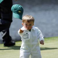 Photo - Scott Stallings's son Finn throws off his cap on the fourth green during the par three competition at the Masters golf tournament Wednesday, April 9, 2014, in Augusta, Ga. (AP Photo/Matt Slocum)