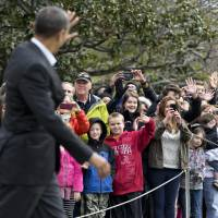 Photo -   Visitors at the White House in Washington greet President Barack Obama as he walks to board his helicopter for a multi-state campaign blitz, on the last weekend before election day, Saturday, Nov. 3, 2012, in Washington. (AP Photo/J. Scott Applewhite)