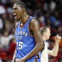 Photo - REACTION: Oklahoma City Thunder's Kevin Durant after making a two-point shot during second half of NBA basketball game against the Miami Heat in Miami, Tuesday,  Nov. 17, 2009. The Thunder won 100-87. (AP Photo/J Pat Carter) ORG XMIT: AAA109