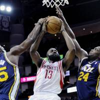 Photo - Houston Rockets' James Harden (13) goes to the basket while double-teamed by Utah Jazz Al Jefferson (25) and Paul Millsap (24) in the first half of an NBA basketball game on Saturday, Dec. 1, 2012, in Houston. (AP Photo/Pat Sullivan) ORG XMIT: HTR101