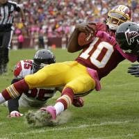 Photo -   Washington Redskins quarterback Robert Griffin III is hit by Atlanta Falcons defensive end Jonathan Massaquoi (96) and defensive tackle Jonathan Babineaux (95) during the second half of an NFL football game in Landover, Md., Sunday, Oct. 7, 2012. (AP Photo/Evan Vucci)