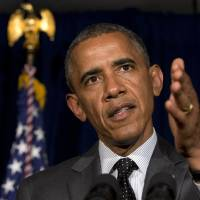 Photo - President Barack Obama speaks at a news conference after meeting with Gov. Rick Perry in Dallas about immigration on Wednesday, July 9, 2014. (AP Photo/Jacquelyn Martin)