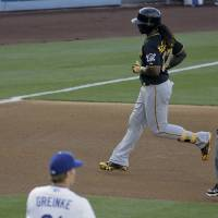 Photo - Pittsburgh Pirates' Andrew McCutchen, right, rounds the bases after his home run as Los Angeles Dodgers starting pitcher Zack Greinke looks on during third inning of a baseball in Los Angeles, Sunday, June 1, 2014. (AP Photo/Chris Carlson)