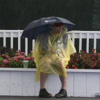 Photo - A spectator waits out a weather delay during the first round of the U.S. Open golf tournament at Merion Golf Club, Thursday, June 13, 2013, in Ardmore, Pa. (AP Photo/Gene J. Puskar)