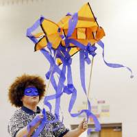 Photo - Above: Drama student Jackson Bugg, 17, dances with a paper fish during an assembly at John Marshall High School in Oklahoma City. Devon Energy gave the school its $25,000 Devon Science Giant grant during an assembly. The money will be used to build a Touch Tank interactive marine ecosystems lab.