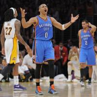 Photo - Oklahoma City Thunder guard Russell Westbrook, center, reacts after missing a last second shot as Los Angeles Lakers center Jordan Hill, left, and Thunder guard Thabo Sefolosha look on in the first overtime of their NBA basketball game, Sunday, April 22, 2012, in Los Angeles. (AP Photo/Mark J. Terrill)  ORG XMIT: LAS301