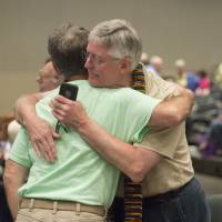 Photo - Gary Lyon, of Leechburg, PA, left, and Bill Samford, of Hawley, PA., celebrate after a vote allowing Presbyterian pastors discretion in marrying same-sex couples at the 221st General Assembly of the Presbyterian Church at Cobo Hall, in Detroit, Thursday, June 19, 2014. The top legislative body of the Presbyterian Church (U.S.A.) voted by large margins to recognize same-sex marriage as Christian in the church constitution, adding language that marriage can be the union of