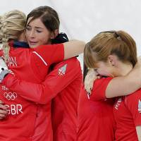 Photo - Britain's women's curling team from left to right, Anna Sloan, Eve Muirhead, Vicki Adams and Claire Hamilton, celebrate after beating Switzerland in the women's curling bronze medal game at the 2014 Winter Olympics, Thursday, Feb. 20, 2014, in Sochi, Russia. (AP Photo/Wong Maye-E)