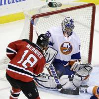 Photo - New York Islanders goalie Evgeni Nabokov (20) of Kazakhstan makes a save off his pads on a shot by New Jersey Devils' Steve Bernier (18) during the second period of an NHL hockey game Monday, April 1, 2013, in Newark, N.J. (AP Photo/Mel Evans)