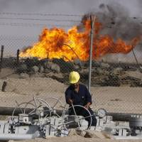 Photo -   An Iraqi worker operates valves at the Rumailah oil refinery near the city of Basra, 340 miles southeast of Baghdad, Iraq.    Nabil al-Jurani -
