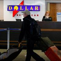 Photo - A Dollar Thrifty employee works behind a counter at Tulsa International Airpor while a traveler passes by. CORY YOUNG/Tulsa World